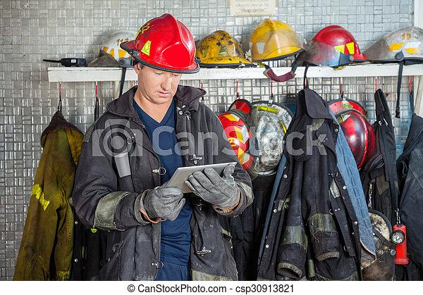 Bombero usando tableta digital en la estación de bomberos - csp30913821