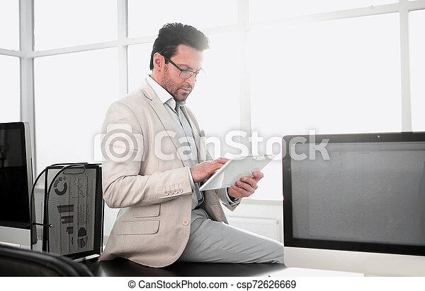 Empresario con tablet digital sentado en la oficina de escritorio. - csp72626669