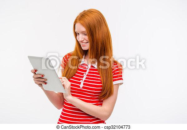 Chica pelirroja sonriente feliz usando tablet - csp32104773