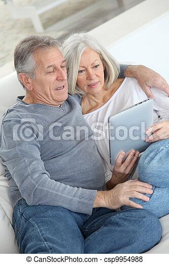 Una pareja mayor sentada en el sofá con tablillas electrónicas - csp9954988