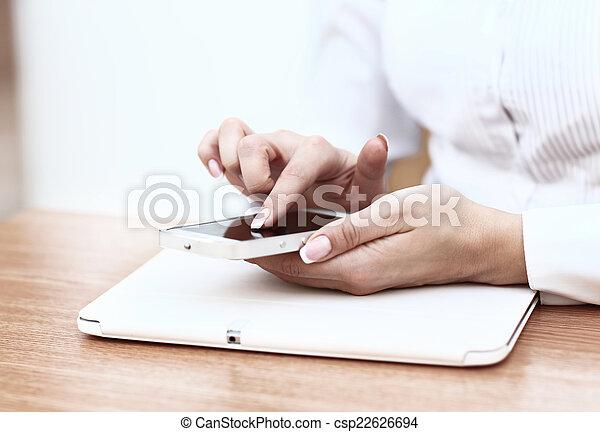 Una joven mujer de negocios que trabaja con aparatos modernos, una tablet digital y un teléfono móvil. - csp22626694