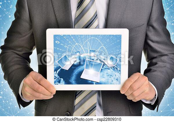 Hände mit Tablet PC. Bild der Erde und Laptops auf dem Bildschirm - csp22809310