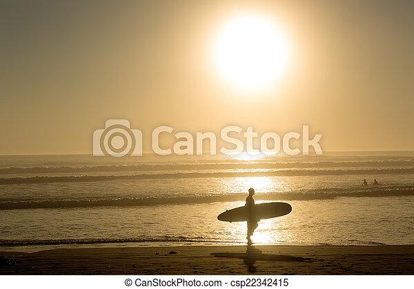 Surfer camina al atardecer - csp22342415