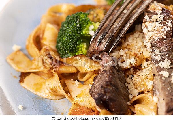 tagliatelli with steak slices on a plate - csp78958416