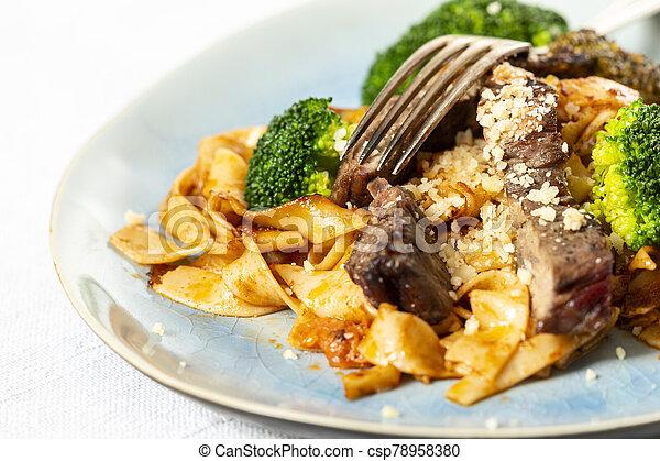 tagliatelli with steak slices on a plate - csp78958380