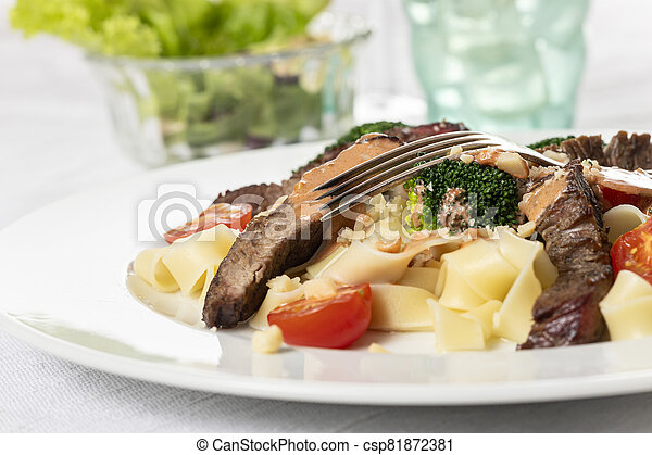 tagliatelli with steak slices on a plate - csp81872381