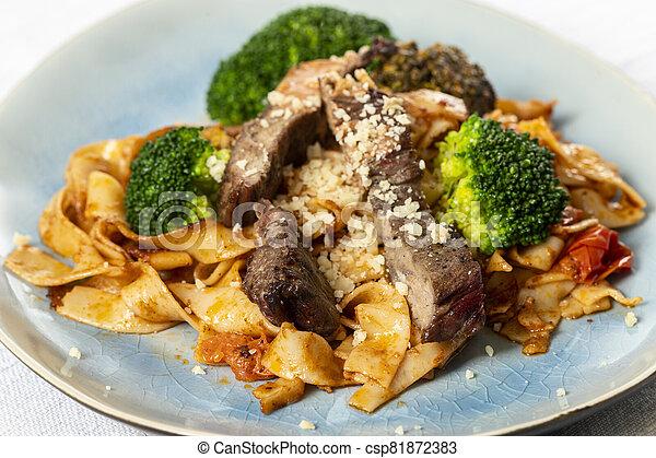 tagliatelli with steak slices on a plate - csp81872383
