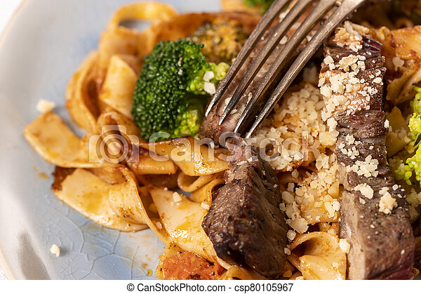 tagliatelli with steak slices on a plate - csp80105967