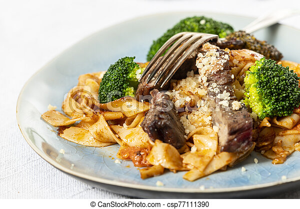 tagliatelli with steak slices on a plate - csp77111390