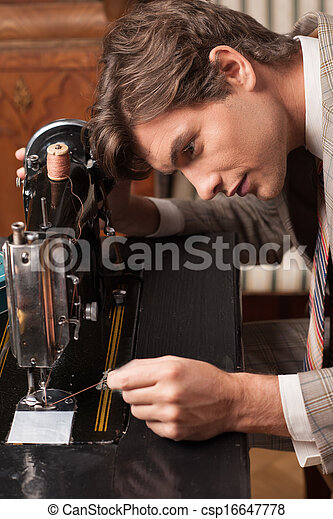 Tailor at work. Cheerful young man working at the tailor shop - csp16647778