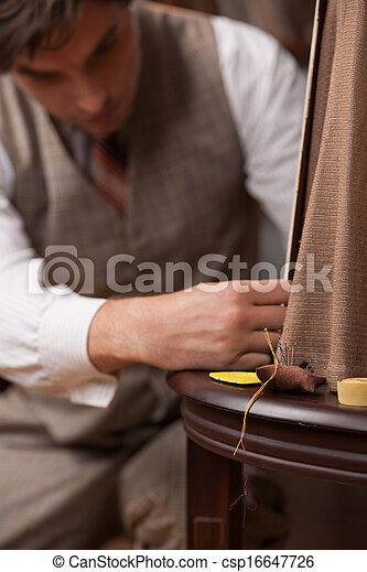 Tailor at work. Confident young tailor sewing clothes at tailor shop - csp16647726