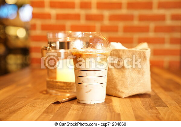 Take away Latte with Brick background on the wood table - csp71204860