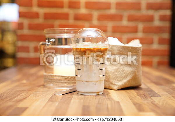Take away Latte with Brick background on the wood table - csp71204858