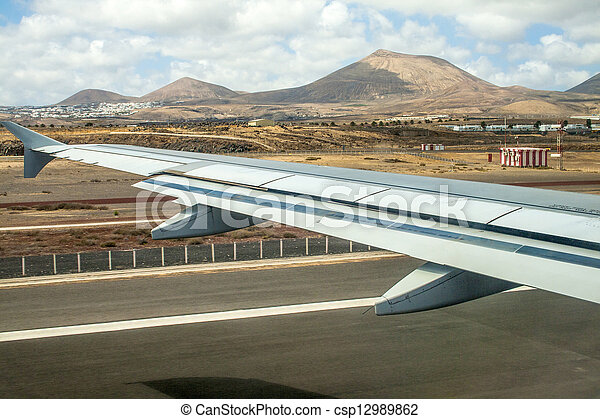 takeoff at airport of Lanzarote with volcanoes at the horizon - csp12989862
