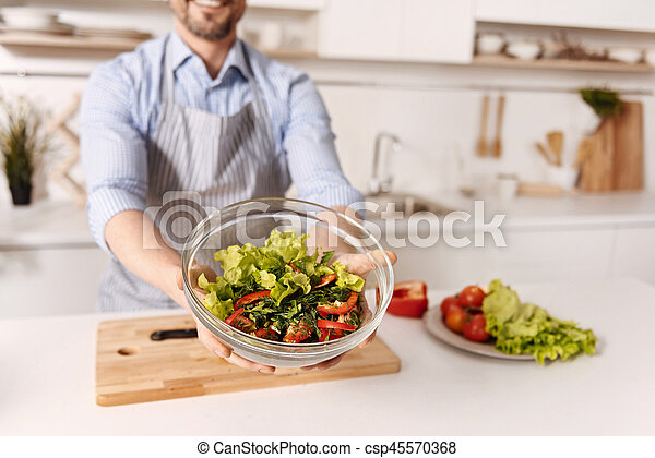 Talented bachelor cooking vegetable salad at home - csp45570368