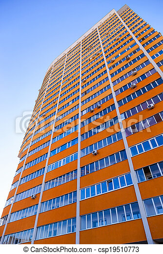 Tall apartment building on blue sky background - csp19510773