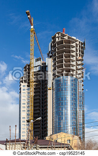 Tall buildings under construction with cranes against a blue sky - csp19523145