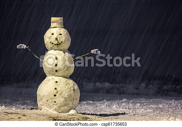 Tall snowman at winter night in the park outdoors. - csp61735653
