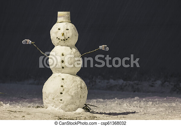 Tall snowman at winter night in the park outdoors. - csp61368032