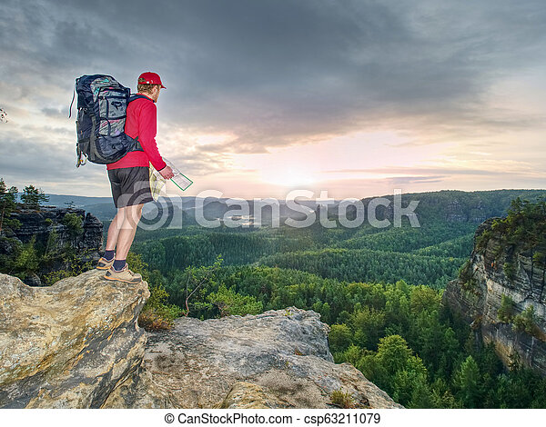 Tall tourist with big backpack looking in paper map. Wild hilly nature - csp63211079