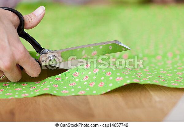 Las manos del diseñador cortando tela con tijeras en el taller - csp14657742