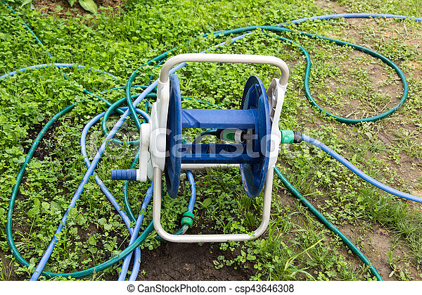 tangled garden hose with a reel on grass - csp43646308