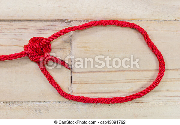 tarbuck knot made with red rope on wooden background. - csp43091762
