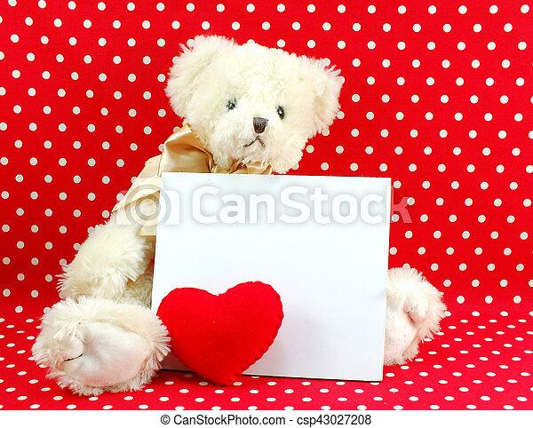 Tarjeta blanca y muñeca de peluche con el corazón rojo en el fondo de lunares rojos - csp43027208
