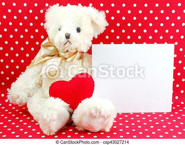 Tarjeta blanca y muñeca de peluche con el corazón rojo en el fondo de lunares rojos - csp43027214
