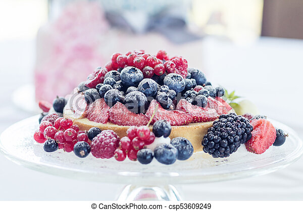 Tasty berry pie with fresh berries on a glass plate. Light background. Shallow depth of field - csp53609249