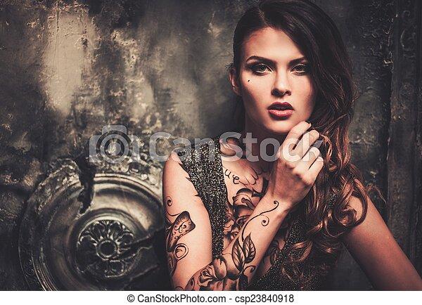 Tattooed beautiful woman in old spooky interior - csp23840918