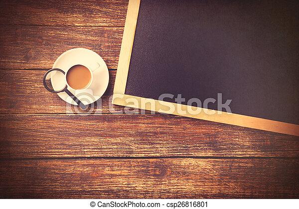 Una taza de café con loupe y pizarra - csp26816801