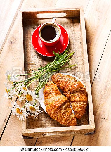 Bandeja de desayuno con croissants, taza de café y flores de margarita - csp28696821