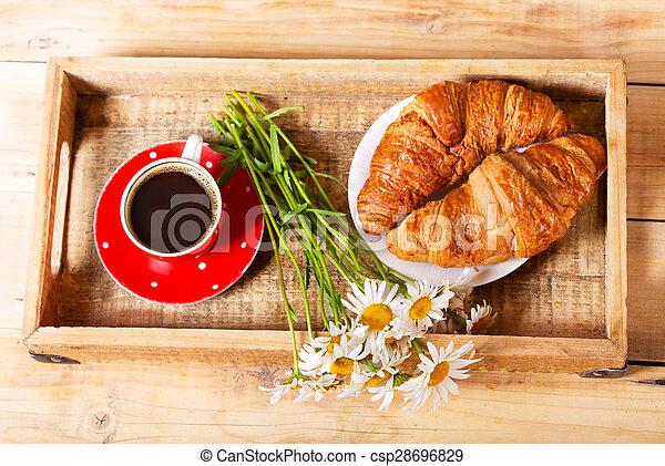 Bandeja de desayuno con croissants, taza de café y flores de margarita - csp28696829