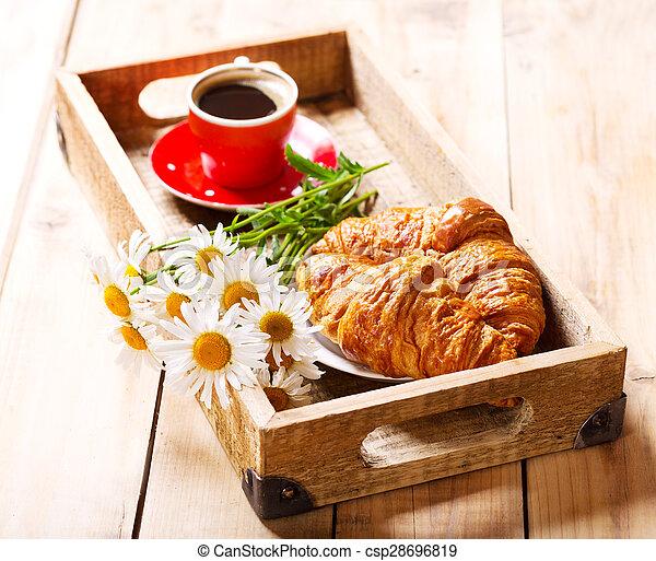 Bandeja de desayuno con croissants, taza de café y flores de margarita - csp28696819