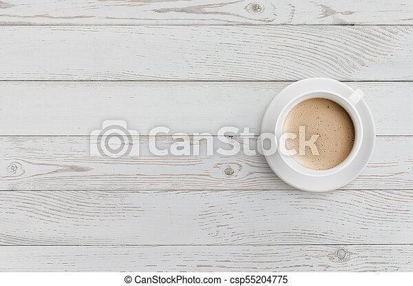 Una taza de café en una mesa de madera blanca - csp55204775