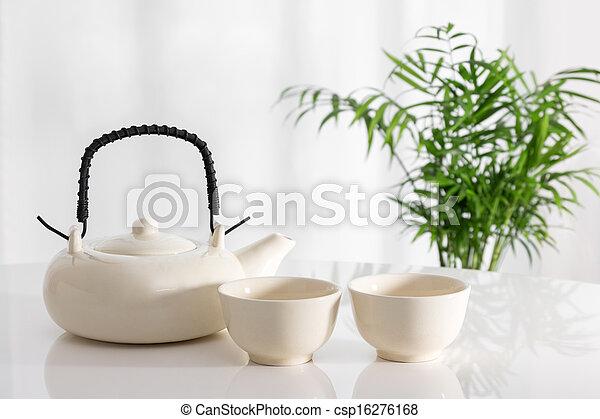 Tetera cerámica y tazas sobre la mesa - csp16276168