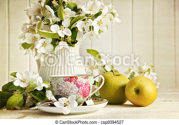 Tea cup with flower blossoms and green apples - csp9394527