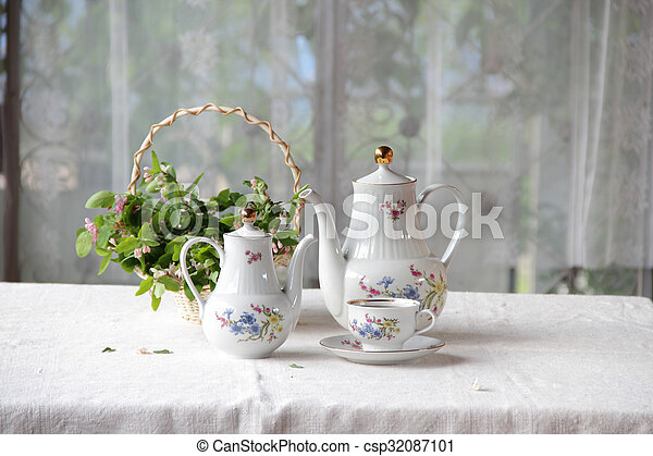 Tea in a cup, tea service on a table with a white cloth - csp32087101
