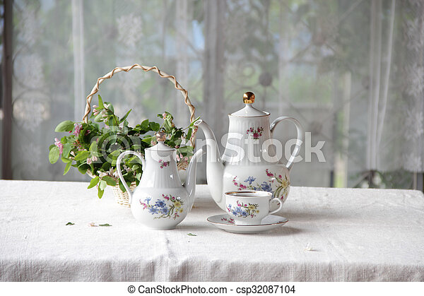 Tea in a cup, tea service on a table with a white cloth - csp32087104