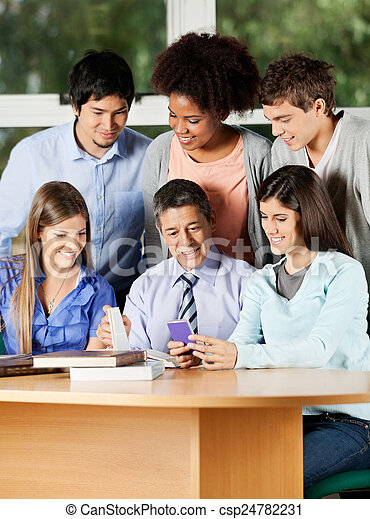 Teacher And Students Discussing Over Mobilephone In Classroom - csp24782231
