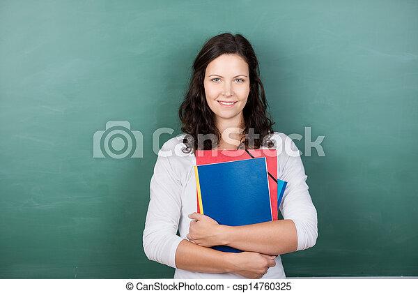 Teacher Holding Files Against Chalkboard - csp14760325