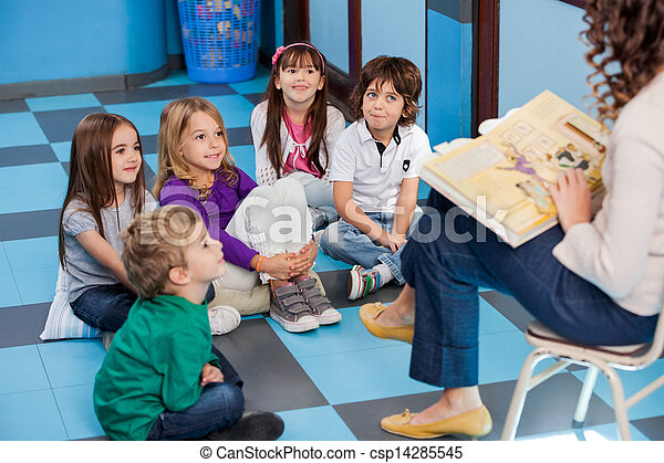 Teacher Reading Story Book To Children - csp14285545