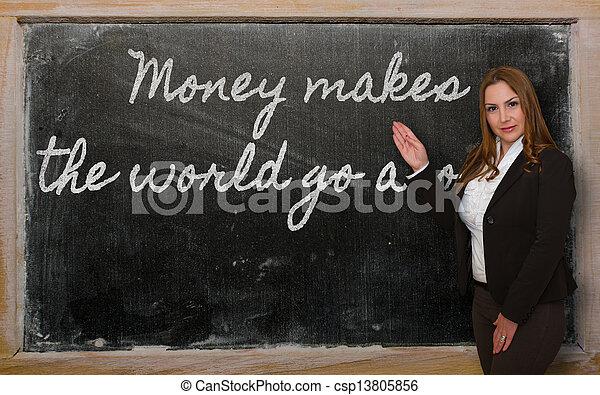 Teacher showing Money makes the world go around on blackboard - csp13805856
