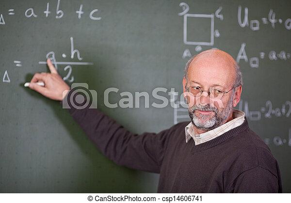 Teacher Teaching Mathematics While Pointing At Blackboard - csp14606741