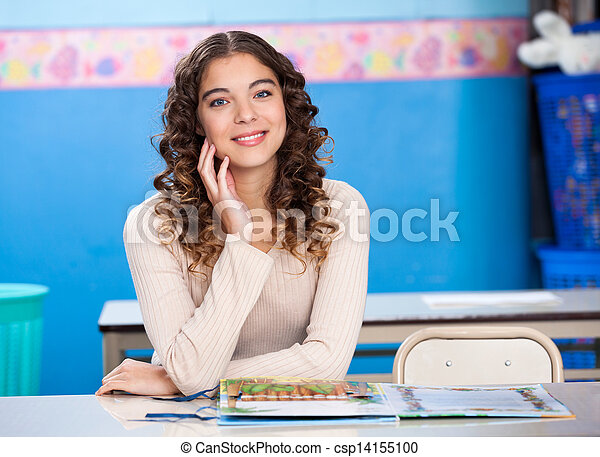 Teacher With Hand On Chin Sitting At Desk - csp14155100