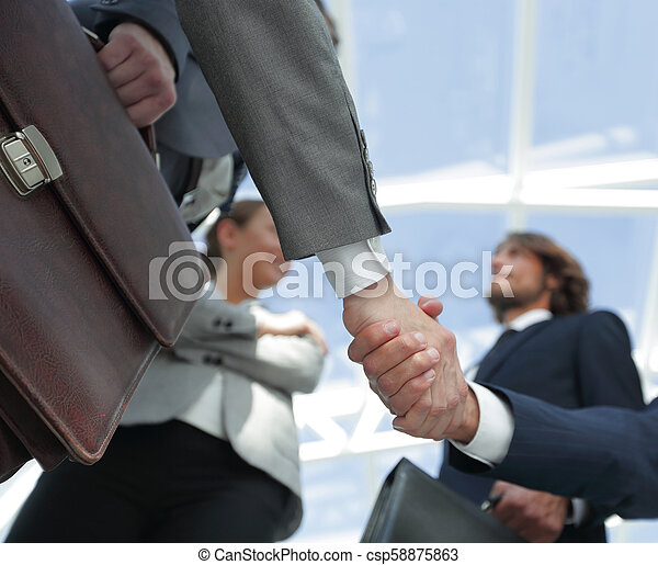 team looking at a business handshake partner. - csp58875863
