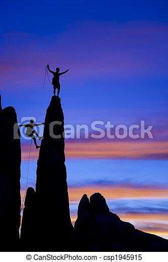Team of rock climbers reaching the summit. - csp1945915