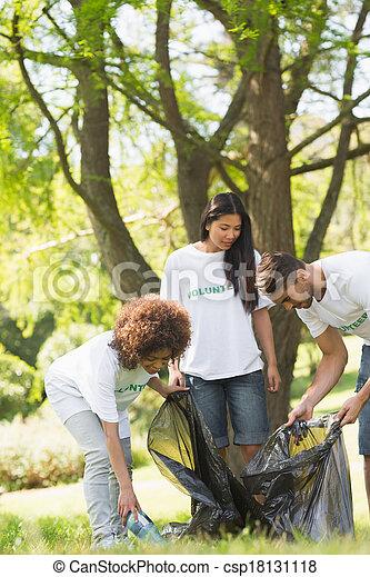 Team of volunteers picking up litter in park - csp18131118