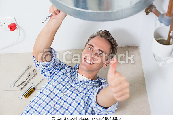 Technician gesturing thumbs up by hot water heater - csp16646065